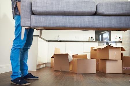 En mann som bærer en sofa, det står også flere flyttekasser plassert på gulvet